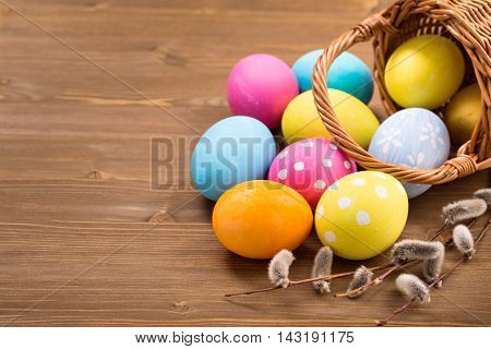 Easter basket with colorful eggs on wooden table