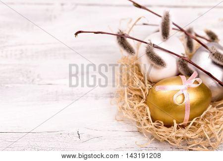 Easter eggs and pussy willow branch on a wooden background right side