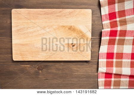 Empty cutting board and checkered napkin on wooden background top view