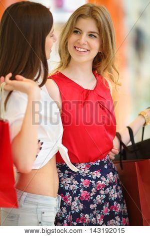 Two pretty girls stand near showcase with bags and look at each other in shopping center. Focus on right woman