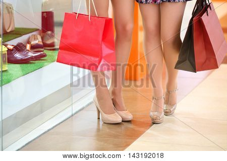 Legs of two girls with bags standing in shopping center, shallow dof