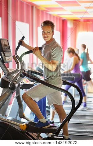 Guy on electronic elliptical trainer among other people in fitness club, focus on man