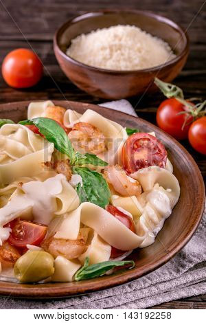 Fettuccine pasta with shrimp, tomatoes and basil cropped shot. Rustic style