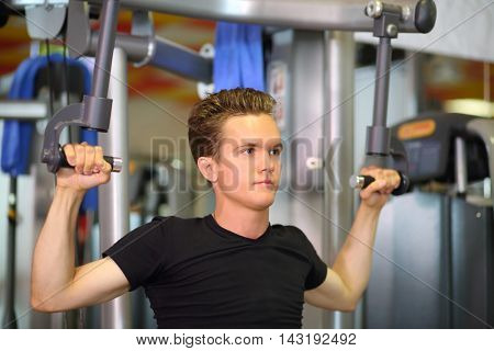Young handsome man lowering weight of fitness machine in fitness club