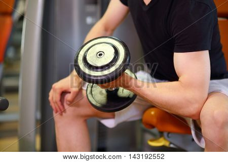 Mans hand, raising and lowering dumbbell in fitness club, close up