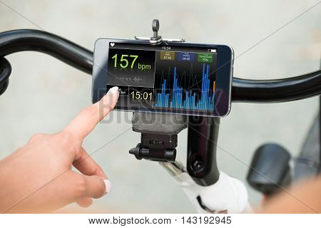 Close-up Of Human Hand Pointing At Smart Phone Showing Heartbeat Rate On Bicycle