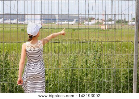 Girl stands near lattice of airport and points of aircrafts, back view