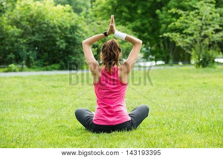 Rear View Of Young Woman Practicing Yoga In Park