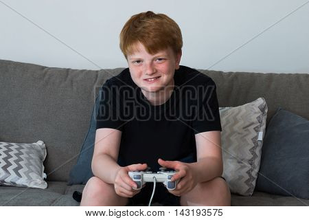 Portrait Of Happy Boy Sitting On Sofa Playing Videogames