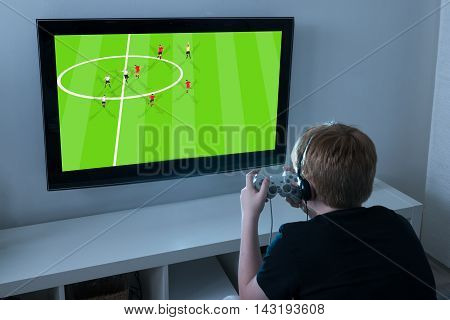 Boy With Joystick Playing Football Videogame On Television At Home