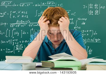 Frustrated Boy In Classroom With Hands On Head