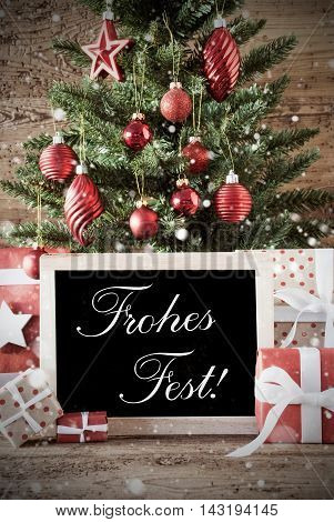 Nostalgic Christmas Card For Seasons Greetings. Christmas Tree With Balls. Gifts Or Presents In The Front Of Wooden Background. Chalkboard With German Text Frohes Fest Means Merry Christmas