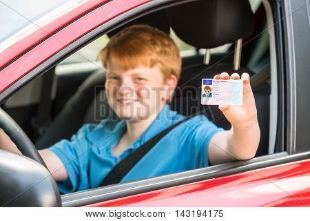 Smiling Boy Sitting Inside Car Showing Driving License