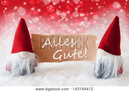 Christmas Greeting Card With Two Red Gnomes. Sparkling Bokeh And Christmassy Background With Snow. German Text Alles Gute Means Best Wishes