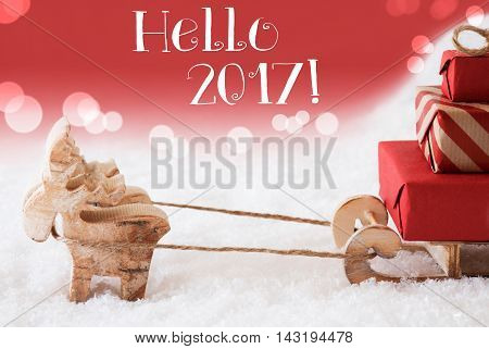 Moose Is Drawing A Sled With Red Gifts Or Presents In Snow. Christmas Card For Seasons Greetings. Red Christmassy Background With Bokeh Effect. English Text Hello 2017 For Happy New Year