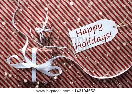 Two Gifts Or Presents With White Ribbon. Red And Brown Striped Wrapping Paper. Christmas Or Greeting Card With Snowflakes. Label With Text Happy Holidays