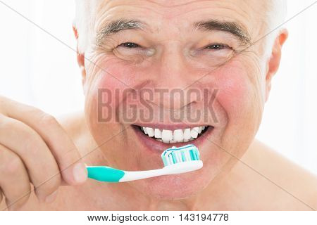Close-up Of A Happy Senior Man Brushing His Teeth With Toothbrush