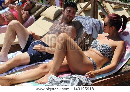 28TH JULY 2016,KABAK,TURKEY: A young english couple together on sunbeds  while on vacation in Kabak in Turkey, 28th july 2016