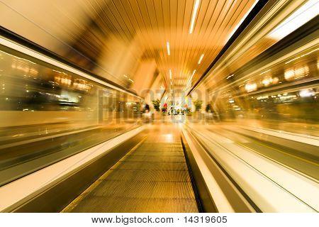 high-speed blue moving escalator inside shopping mall