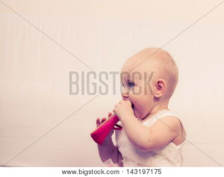 Infant in time of teething. Sweet cute baby girl biting chewing red shoe. Young adorable child portrait.