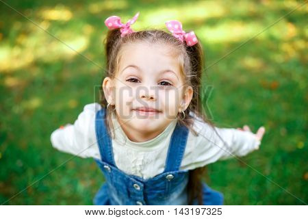 Sweet little girl outdoors with curly hair in two long tails. Closeup portret.
