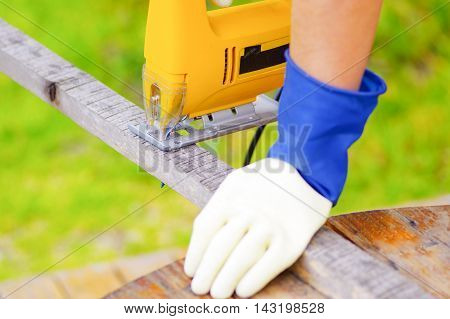 hand holding a piece of wood while the electric jigsaw cuts it.
