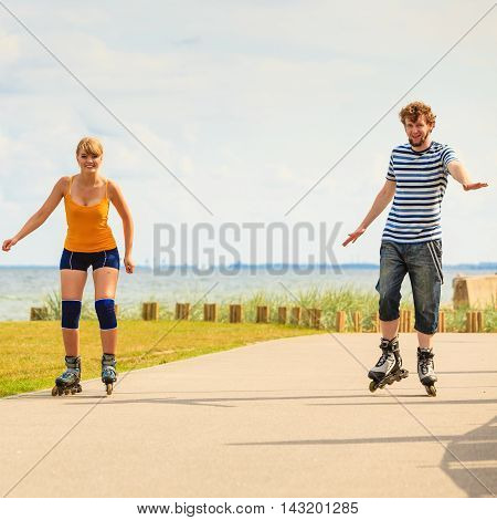 Holidays active people and friendship concept. Young fit couple on roller skates riding outdoors on sea shore woman and man rollerblading together on the promenade