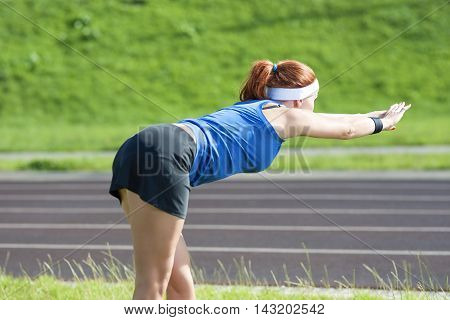 Young Red Haired Ginger Caucasian Female in Athletic Sportgear Making Arms Stretching Excercises Outdoors. Horizontal Image Orientation