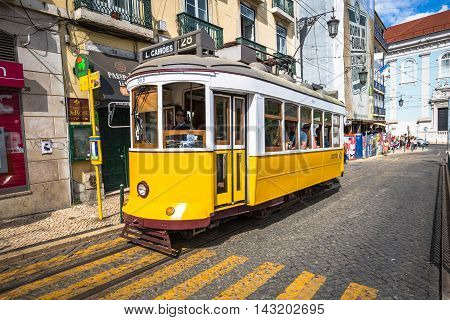 LisboaPortugal-April 122015: A traditional tram is making its way through a narrow street in Lisbon Portugal on June 3 2013. The five urban tramway lines mainly serve as a tourist attraction.