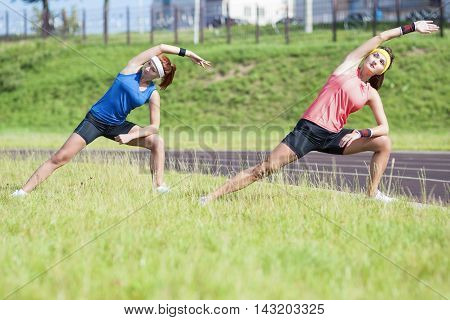 Two Young Feale Sportswomen Having Stretching Exercises Outdoors.Horizontal Image