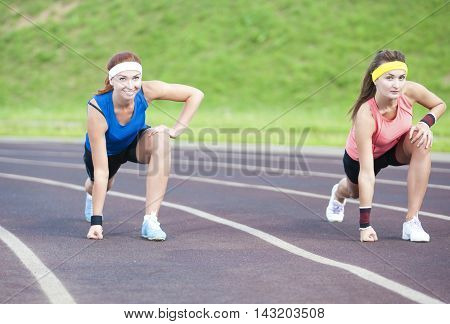 Two Caucasian Sportswomen Standing Prior to Running On Sport Venue Outdoors. Horizontal Image Orientation