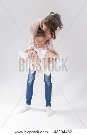 Family Concepts and Ideas. Young Mother and Her Little Cute Daughter Playing Together. Posing Against White. Vertical Image