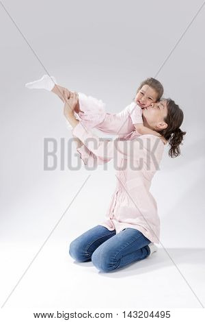 Love and Relationships Concepts. Portrait of Young Mother Kissing Her Child with Positive Expression. Vertical Image Orientation