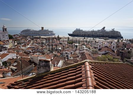 LISBON, PORTUGAL - September 30, 2015: View over the roofs of the old city towards the cruise ship terminal with two ships docked on September 28, 2015 in Lisbon, Portugal