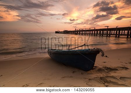 the boat on low tide beach when burst sunset