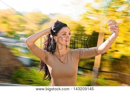young beautiful woman taking selfie outdoor on the carousel
