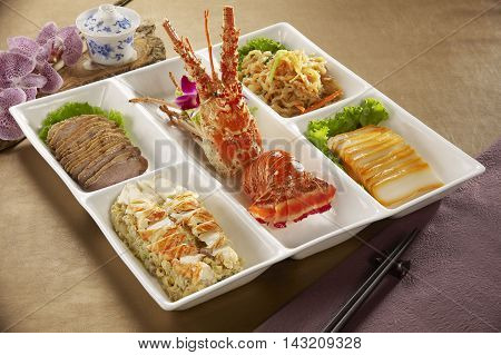 Bento of lobsters sliced pork rice and vegetables in Japanese restaurant