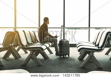 A guy sitting alone in airport waiting for flight, vintage tone