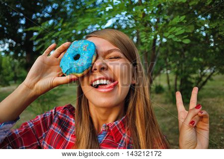 Cheerful girl holding a donut in hand closing one eye. Delicious.