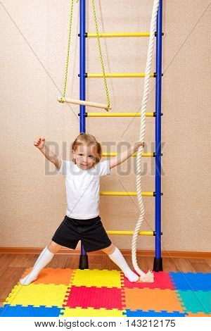 Little girl posing next to the Wall bars. Sports Equipment. Children's sports.