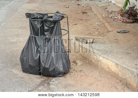 Black garbage bag. Trash bag black plastic garbage bags front of house.