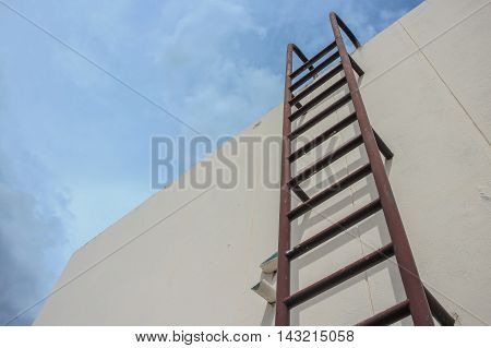 Old vertical industrial metal rusted ladder. Staircase to Water tank no safety rails. sky background with copy space.