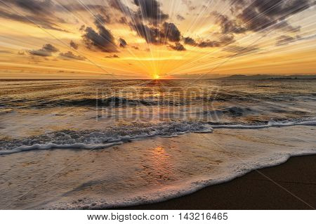 Ocean sunset rays is a brightly lit golden orange seascape with a burst of sun beams as a gentle wave rolling to the shore.