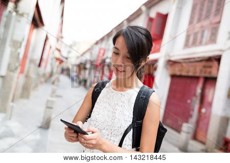 Woman using mobile phone at outdoor of Macao city