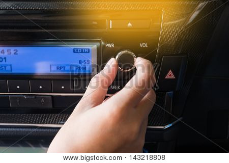 Woman using black car volume audio control.