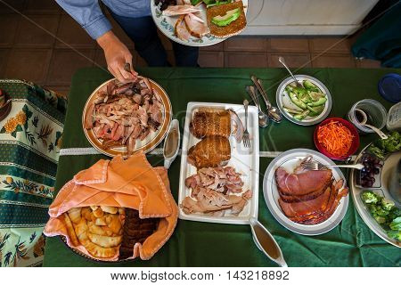 A portion of a buffet table set for Thanksgiving. A person is getting turkey for their plate.