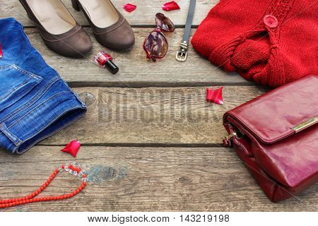 Women's autumn clothing and accessories: red sweater, jeans, handbag, beads, sunglasses, nail polish, shoes, belt on wooden background. Toned image.