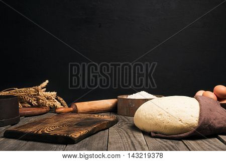 Kitchen table with free place for your product and ingredients for cooking bread or pizza. Yeast dough flour eggs wheat and rolling pin on the wooden table