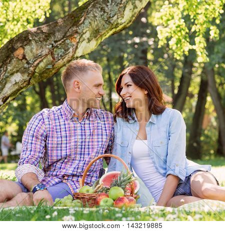 Attractive and cheerful couple staying healthy while having a picnic on fresh air.