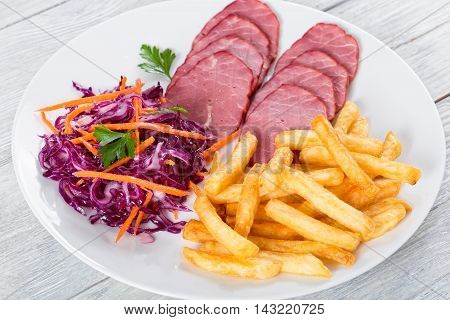 sliced smoked veal fillet french fries and red cabbage salad with carrots cut into strips and parsley dressing with vinegar and olive oil on white rustic boards view from above close-up selective focus